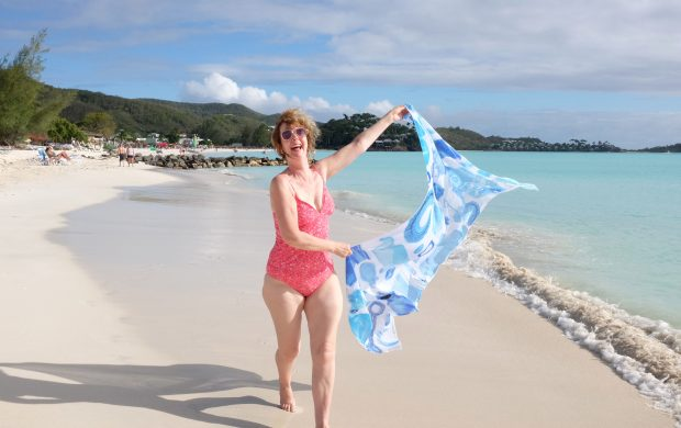 Happy Sarong lady running on Jolly Harbour beach Antigua